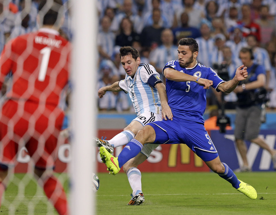 Photo - Argentina's Lionel Messi (10) challenges Bosnia's Sead Kolasinac (5) for the ball in front of Bosnia's goalkeeper Asmir Begovic (1) during the group F World Cup soccer match between Argentina and Bosnia at the Maracana Stadium in Rio de Janeiro, Brazil, Sunday, June 15, 2014. (AP Photo/Thanassis Stavrakis)
