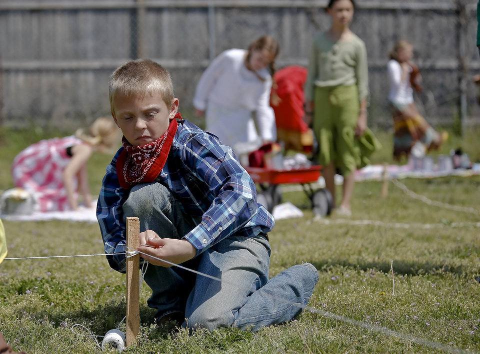 Weston Rutledge ties off the string to claim his land during the Oklahoma Land Run celebration at Mustang Trails Elementary on Monday, April 22, 2013, in Mustang, Okla.   Photo by Chris Landsberger, The Oklahoman