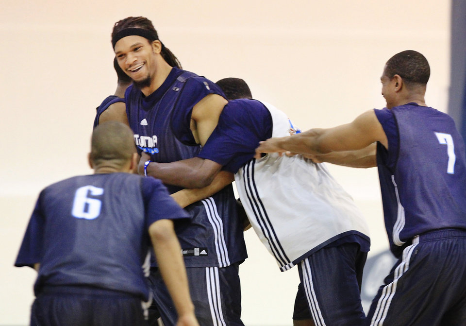 Photo - NBA BASKETBALL: Oklahoma City Thunder players swarm Etan Thomas after he won a shooting contest at the end of practice at the Thunder practice facility Monday, April 26, 2010,  before the team traveled to California to play in Game 5 of the first round of the NBA playoffs against the Los Angeles Lakers.   Hugging Thomas is Jeff Green.  #6 is Eric Maynor.  #7 is Kevin Ollie. Photo by Jim Beckel, The Oklahoman ORG XMIT: KOD
