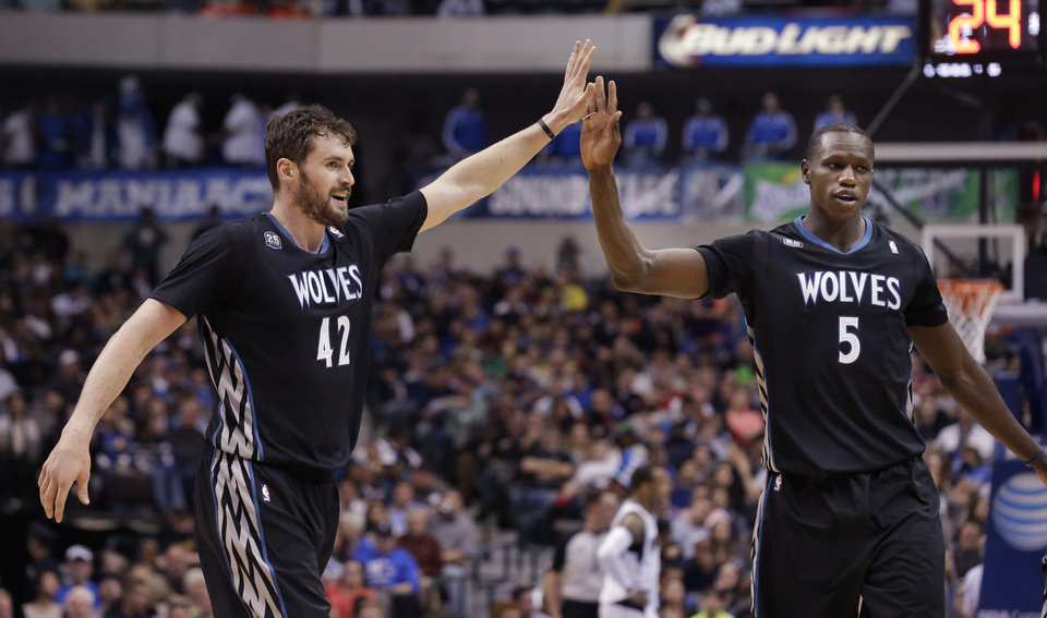 Photo - Minnesota Timberwolves forward Kevin Love (42) celebrates with teammate Gorgui Dieng (5) during the second half an NBA basketball game against the Dallas Mavericks Wednesday, March 19, 2014, in Dallas. The Timberwolves won in overtime 123-122. (AP Photo/LM Otero)