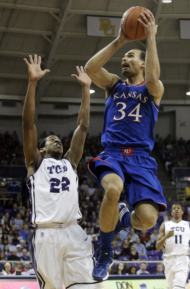 Photo - Kansas forward Perry Ellis (34) attempts a shot as TCU's Jarvis Ray (22) defends in the first half of an NCAA college basketball game, Saturday, Jan. 25, 2014, in Fort Worth, Texas. (AP Photo/Brandon Wade)