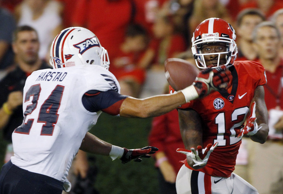 Photo -   Georgia receiver Tavarres King (12) makes a catch for a big gain as Florida Atlantic safety Brent Harstad (24) defends during the first half of an NCAA college football game Saturday, Sept. 15, 2012, in Athens, Ga. (AP Photo/John Bazemore)