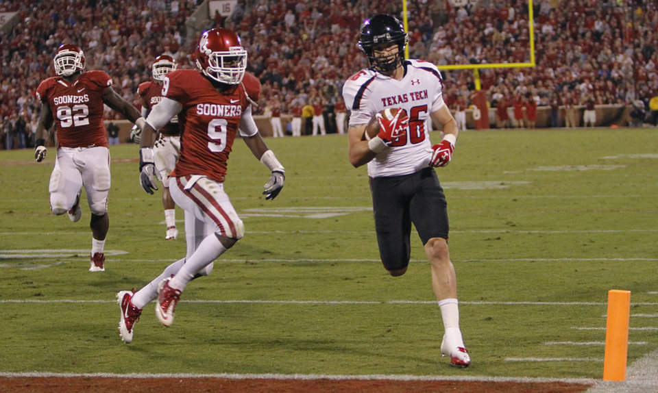 Photo - Texas Tech's Alex Torres (86) scores a touchdown in front of Oklahoma's Gabe Lynn (9) during the college football game between the University of Oklahoma Sooners (OU) and Texas Tech University Red Raiders (TTU) at the Gaylord Family-Oklahoma Memorial Stadium on Sunday, Oct. 23, 2011. in Norman, Okla. Photo by Chris Landsberger, The Oklahoman