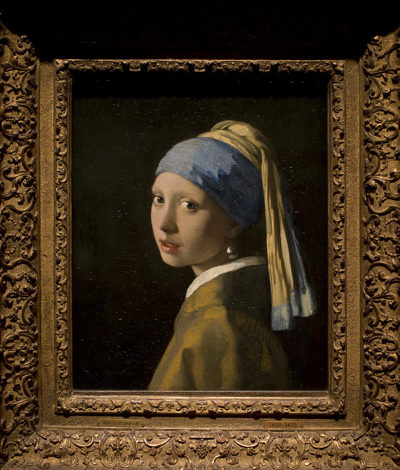 Photo - This reproduction shows Johannes Vermeer's Girl with a Pearl Earring (painted approximatetely 1665) at the renovated Mauritshuis museum during a preview for the press in The Hague, Netherlands, Friday, June 20, 2014. The Mauritshuis reopens after a two-year renovation that allowed its masterpieces, including Vermeer's The Girl with the Pearl Earring to be seen by record-setting crowds abroad. The public will have access for free from 8 pm till midnight on Friday June 27th after the official ceremonial opening and from June 28 onwards the museum will revert to regular opening hours. (AP Photo/Peter Dejong)