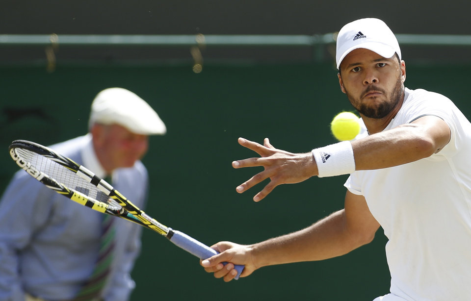 Photo - Jo-Wilfried Tsonga of France plays a return to Jimmy Wang of Chinese Taipei during their men's singles match at the All England Lawn Tennis Championships in Wimbledon, London, Friday, June 27, 2014. (AP Photo/Alastair Grant)