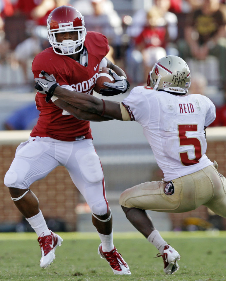 Photo - Oklahoma's Brennan Clay (21) tries to get past Florida State's Greg Reid (5) during the second half of the college football game between the University of Oklahoma Sooners (OU) and the Florida State University Seminoles (FSU) on Sat., Sept. 11, 2010, in Norman, Okla.  Photo by Chris Landsberger, The Oklahoman