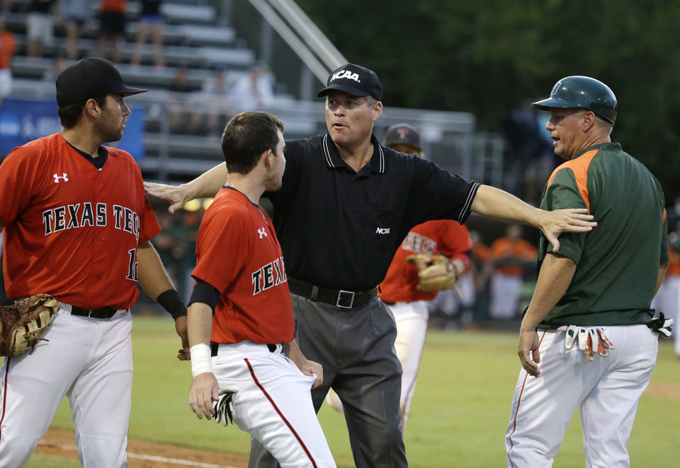 Photo - An umpire, center, separates Texas Tech infielder Eric Gutierrez, left, and Miami assistant coach Gino DiMare, right, as they argue after Miami's David Thompson was out at third in the third inning during an NCAA college baseball regional tournament in Coral Gables, Fla., Sunday, June 1, 2014. Gutierrez, Texas Tech coach J-Bob Thomas and DiMare were ejected. (AP Photo/Lynne Sladky)