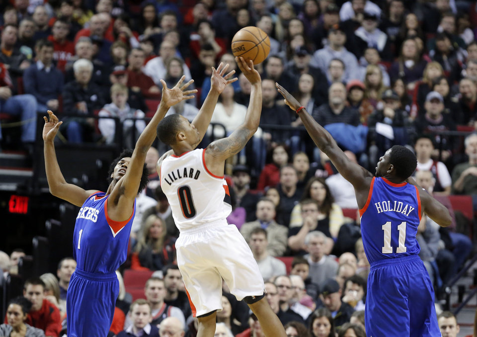 Portland Trail Blazers guard Damian Lillard, middle, shoots against Philadelphia 76ers guards Nick Young, left, and Jrue Holiday during the first quarter of an NBA basketball game in Portland, Ore., Saturday, Dec. 29, 2012.(AP Photo/Don Ryan)