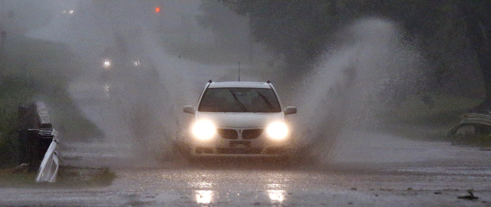 Photo - A car drive through water flooding over a bridge in Oklahoma City, Okla. on Wednesday, May 6, 2015.  Photo by Chris Landsberger, The Oklahoman