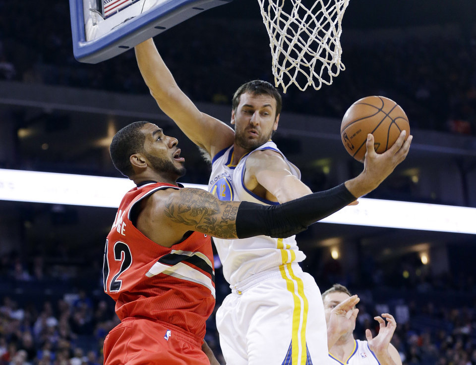 Photo - Portland Trail Blazers' LaMarcus Aldridge, left, goes up for a layup as Golden State Warriors' Andrew Bogut defends during the first half of an NBA basketball game on Sunday, Jan. 26, 2014, in Oakland, Calif. (AP Photo/Marcio Jose Sanchez)