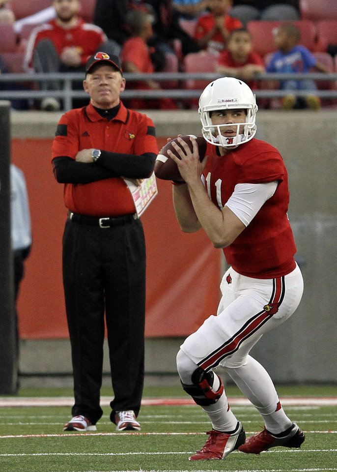 Photo - Louisville quarterback Will Gardner (11) drops back to pass as head coach Bobby Petrino watches in the background during a NCAA college spring football game in Louisville, Ky., Friday, April 11, 2014.  (AP Photo/Garry Jones)