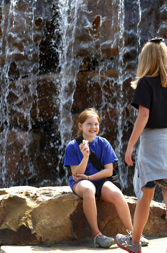 Hannah Gage, 11, a fifth grader student at Deer Creek Intermediate School, eats an ice cream cone and talks to a classmate while resting on some rocks in the Centennial Waterfall area at the state fair on Monday, Sep. 17, 2012. The students were on a field trip. Photo by Jim Beckel, The Oklahoman.