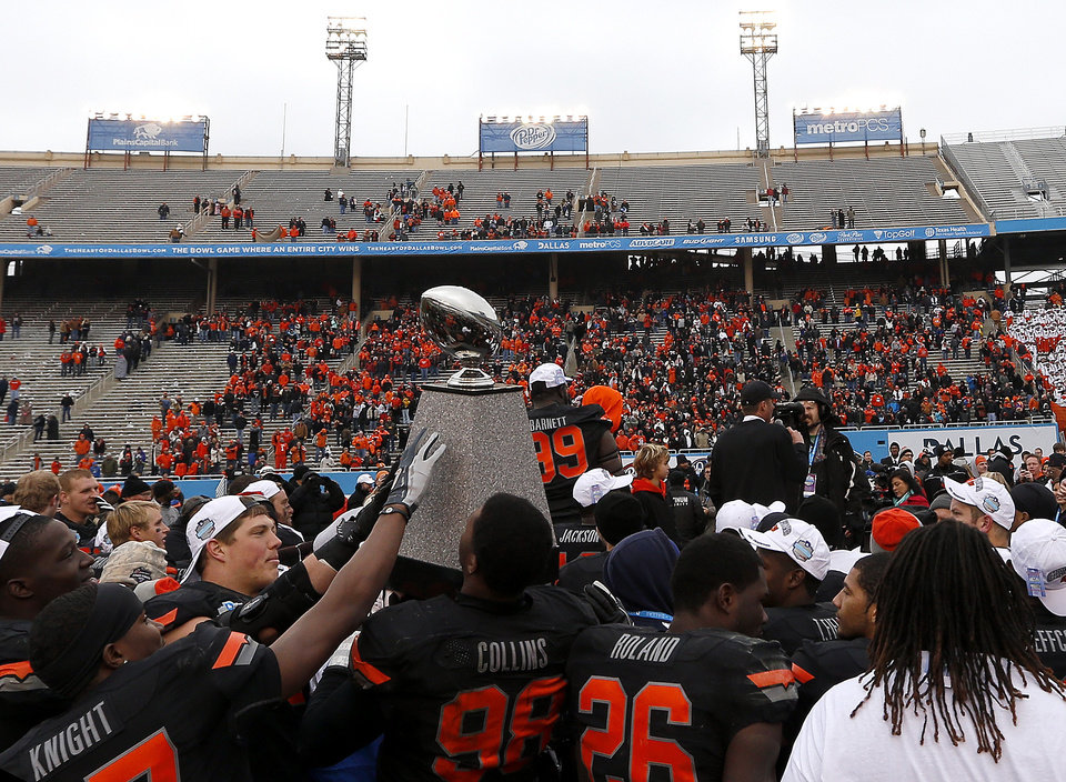 Photo - Oklahoma State holds the Heart of Dallas trophy following the Heart of Dallas Bowl football game between the Oklahoma State University (OSU) and Purdue University at the Cotton Bowl in Dallas,  Tuesday,Jan. 1, 2013. Photo by Sarah Phipps, The Oklahoman