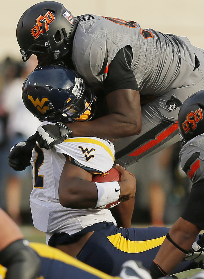 Photo - Oklahoma State's Ryan Robinson (96) sacks West Virginia's Geno Smith (12) during a college football game between Oklahoma State University (OSU) and West Virginia University (WVU) at Boone Pickens Stadium in Stillwater, Okla., Saturday, Nov. 10, 2012. Photo by Nate Billings, The Oklahoman