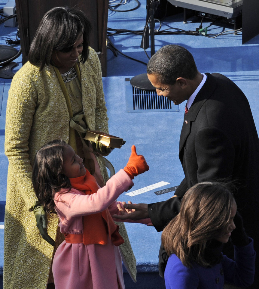 Photo - President Barack Obama, right, is congratulated by daughter Sasha, lower left, as first lady Michelle Obama looks on after taking the oath of office at the U.S. Capitol in Washington, Tuesday, Jan. 20, 2009.  (AP Photo/Susan Walsh)