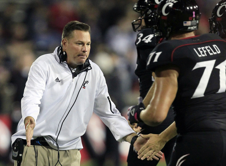 FILE - In this Oct. 13, 2012, file photo, Cincinnati head coach Butch Jones, left, slaps hands with his players as they run off the field after scoring a touchdown in the second half of an NCAA college football game against Fordham in Cincinnati. The bowl-bound Bearcats wait to hear from coach Jones about whether he\'ll stay or head off to either Purdue or Colorado. (AP Photo/Al Behrman, File)