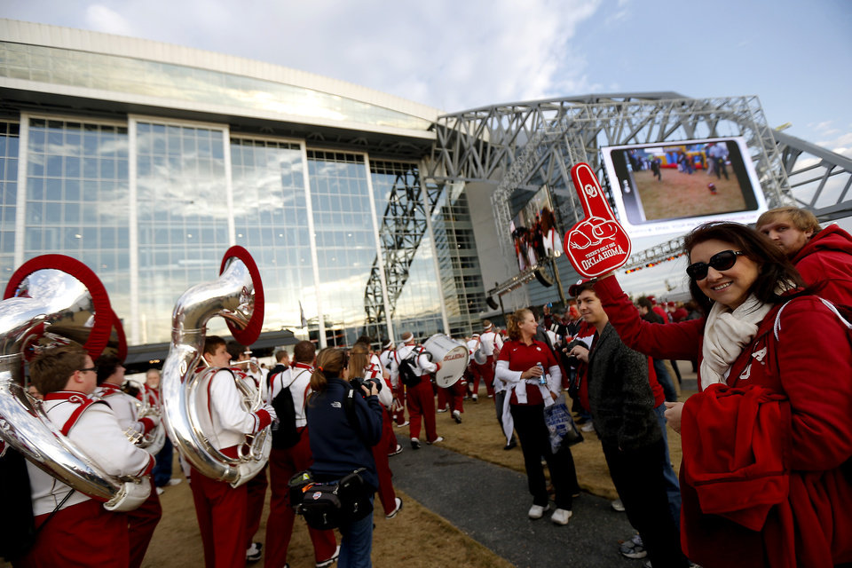 Photo - Surel Garza, of Fort Worh, Texas, whose son is in the band, cheers for the Pride of Oklahoma as they walk to Cowboys Stadium before the Cotton Bowl college football game between the University of Oklahoma (OU)and Texas A&M University at Cowboys Stadium in Arlington, Texas, Friday, Jan. 4, 2013. Photo by Bryan Terry, The Oklahoman