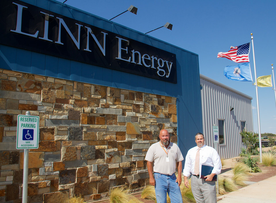 Paul D. Lamle, district production superintendent for Linn Energy, and Shane Frye, Elk City�s director of economic development, are in front of Linn�s Elk City district office.
