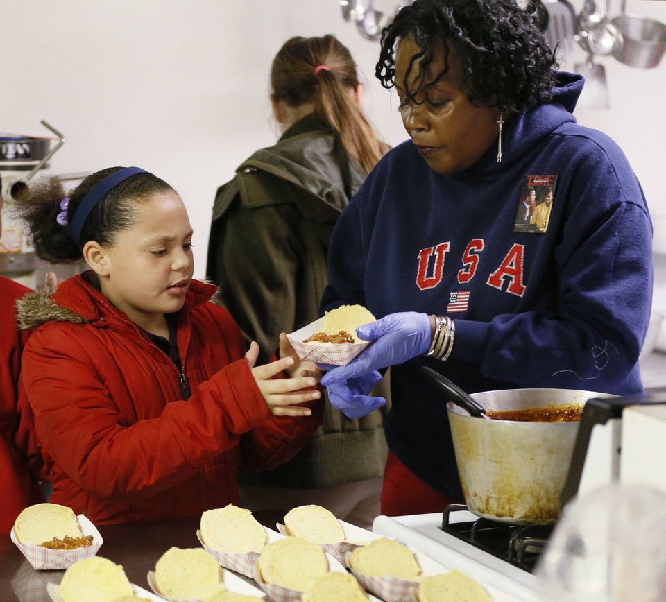 Photo - Volunteer Jann Lenox gives brisket sandwich to Aaliyah Jefferson, 9, during J.A.M. Youth Ministry at Prospect Baptist Church, 2809 N Missouri Ave., in Oklahoma City, Wednesday, Nov. 14, 2012. Photo by Nate Billings, The Oklahoman