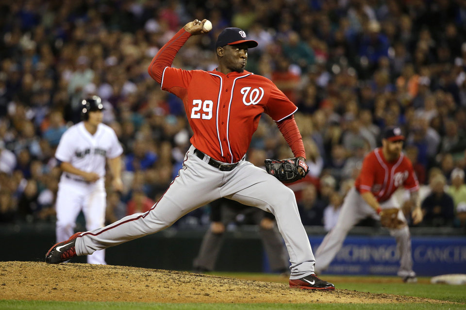 Photo - With a man on first, Washington Nationals closing pitcher Rafael Soriano throws against the Seattle Mariners in the ninth inning of a baseball game, Saturday, Aug. 30, 2014, in Seattle. Soriano picked up a save as the Nationals defeated the Mariners 3-1. (AP Photo/Ted S. Warren)