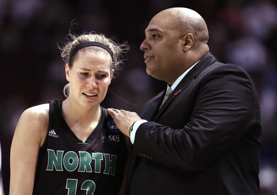 Photo - North Dakota coach Travis Brewster, right, comforts Madi Buck after losing 70-55 to Texas A&M in a first-round NCAA women's basketball game Sunday, March 23, 2014, in College Station, Texas. A&M will face James Madison in the second round Tuesday night. (AP Photo/Pat Sullivan)