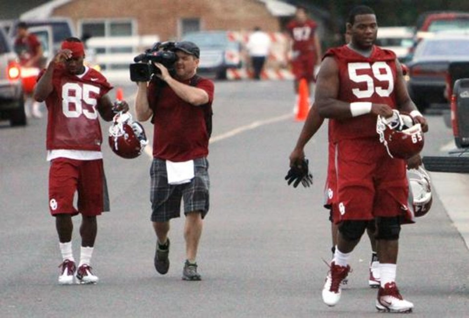 Photo -  Film crews document the 6:45 a.m. arrival of Ryan Broyles (85) as he heads to the University of Oklahoma (OU) Sooners first practice on Thursday, August 4, 2011, in Norman, Okla.  At right is offensive tackle Donald Stephenson (59). Photo by Steve Sisney, The Oklahoman
