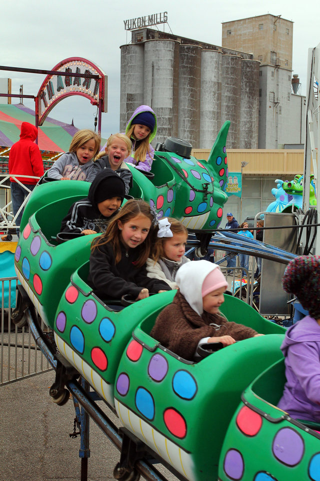 Photo - Children go for a spin on a ride at the carnival during the 47th annual Czech Festival Saturday in Yukon. PHOTO BY HUGH SCOTT FOR THE OKLAHOMAN