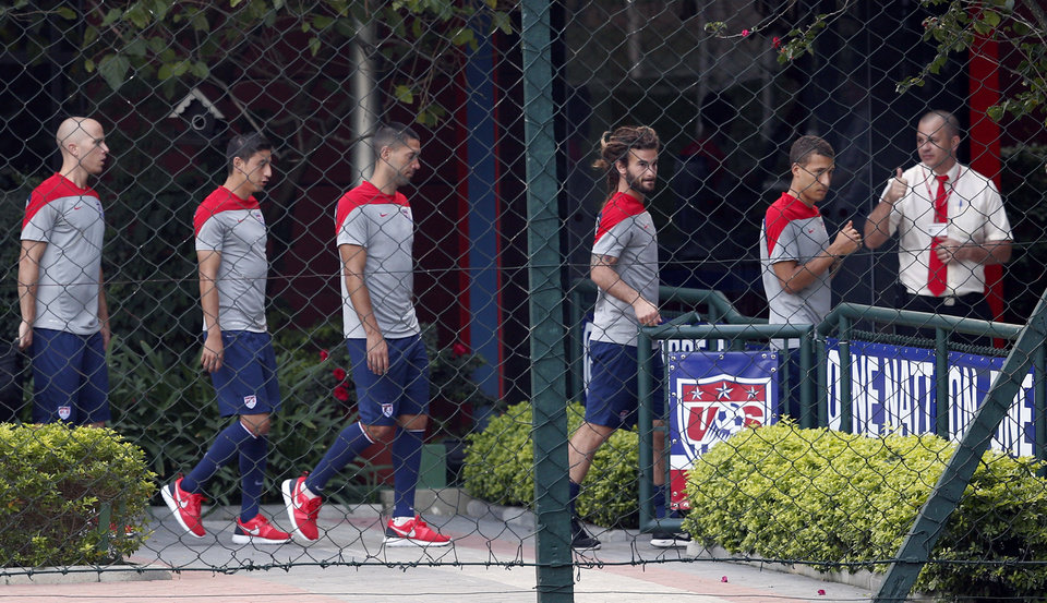 Photo - United States players walk toward an indoor workout during a training session in Sao Paulo, Brazil, Tuesday, June 17, 2014.  The United States will play against Portugal in group G of the 2014 soccer World Cup on June 22. (AP Photo/Julio Cortez)