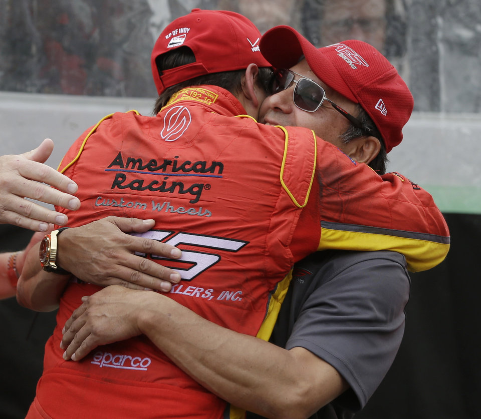 Photo - Sebastian Saavedra, of Colombia, hugs Wilson Saavedra after winning the pole for the inaugural Grand Prix of Indianapolis IndyCar auto race at the Indianapolis Motor Speedway in Indianapolis, Friday, May 9, 2014. (AP Photo/Darron Cummings)