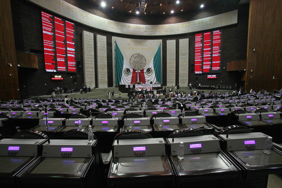 Photo - Opposition lawmakers occupy the podium Wednesday at the National Congress in protest against the newly approved energy reform bill in Mexico City. AP Photo  Marco Ugarte