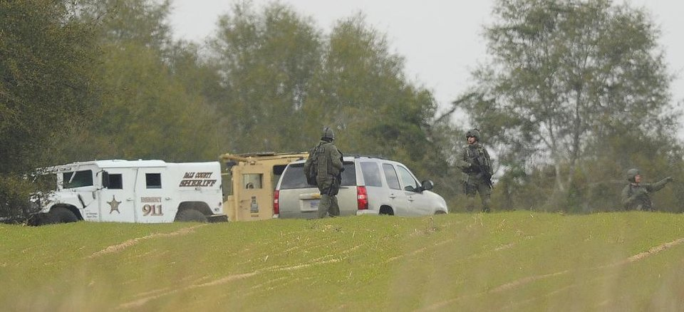 Photo - Armed law enforcement personnel station themselves near the property of Jimmy Lee Sykes, Monday, Feb. 4, 2013 in Midland City, Ala. Officials say they stormed a bunker in Alabama to rescue a 5-year-old child being held hostage there after Sykes, his abductor, was seen with a gun. (AP Photo/AL.com, Joe Songer)