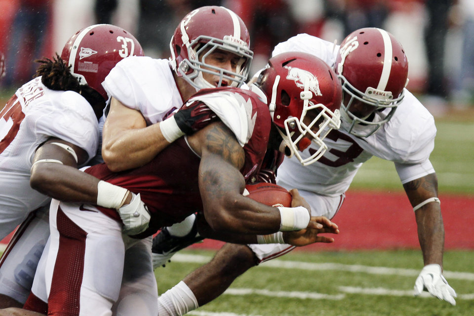 Photo -   Arkansas running back Knile Davis pushes through Alabama defensive backs Robert Lester (37), Vinnie Sunseri (3) and Deion Belue, right, during the second quarter of an NCAA college football game in Fayetteville, Ark., Saturday, Sept. 15, 2012. (AP Photo/Danny Johnston)