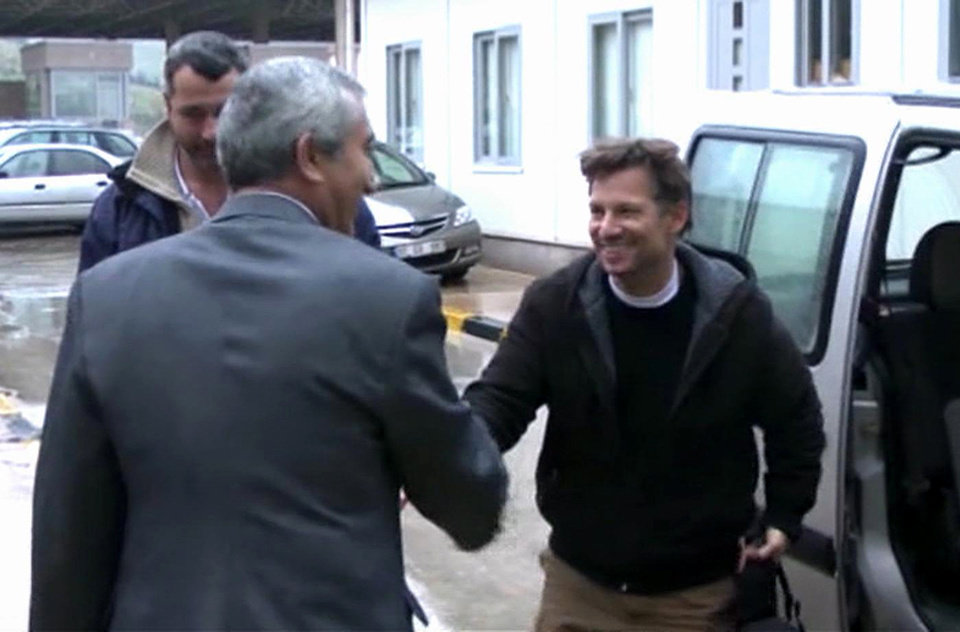 Photo - In this image made from video, NBC chief foreign correspondent Richard Engel, right, shakes hands with an unidentified person after crossing back into Turkey, after they were freed unharmed following a firefight at a checkpoint after five days of captivity inside Syria, in Cilvegozu, Turkey, Tuesday, Dec. 18, 2012. Engel told the Turkish news agency Anadolu that he and his colleagues are