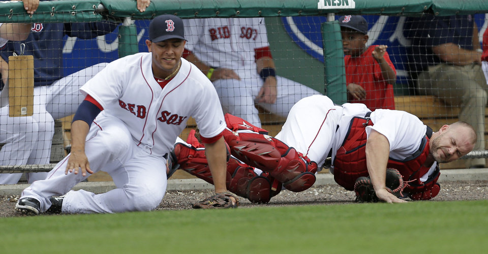 Photo - Boston Red Sox catcher David Ross, right, and third baseman Carlos Rivero collide while chasing a pop foul by Minnesota Twins' Josh Willingham during the sixth inning of an exhibition baseball game in Fort Myers, Fla., Saturday, March 29, 2014. (AP Photo/Gerald Herbert)
