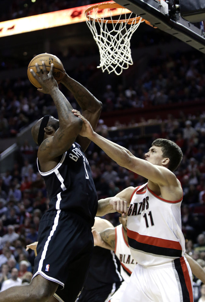 Photo - Brooklyn Nets forward Reggie Evans, left, is fouled while shooting by Portland Trail Blazers center Meyers Leonard during the first quarter of an NBA basketball game in Portland, Ore., Wednesday, March 27, 2013.(AP Photo/Don Ryan)
