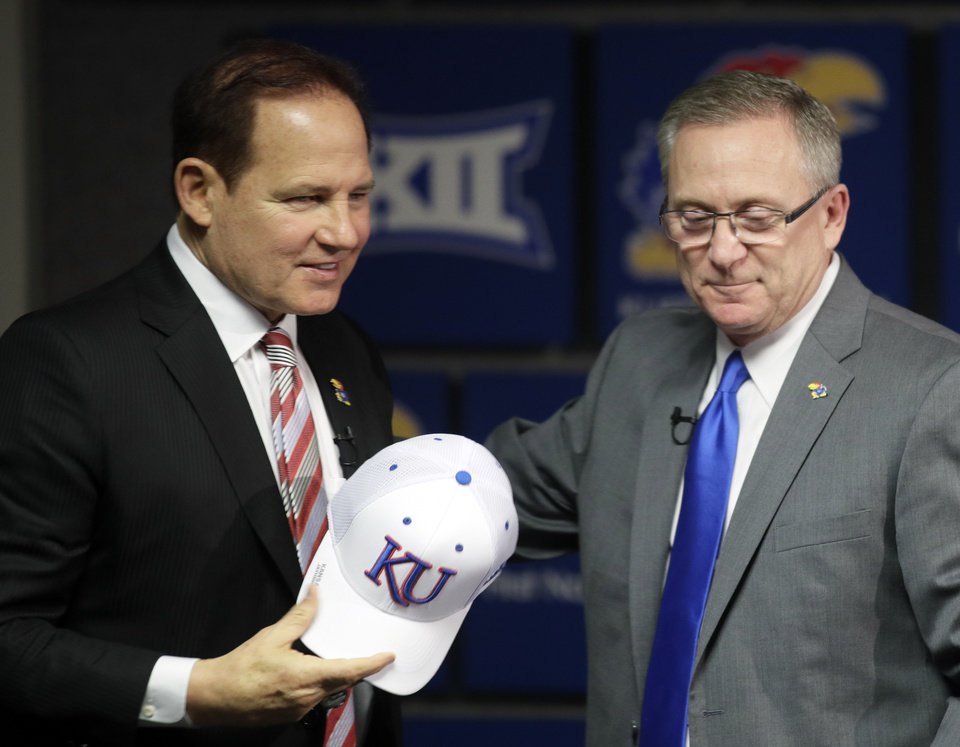 Photo -  Les Miles, left, is introduced as Kansas football coach by athletic director Jeff Long during a news conference Sunday in Lawrence, Kan. [AP PHOTO]