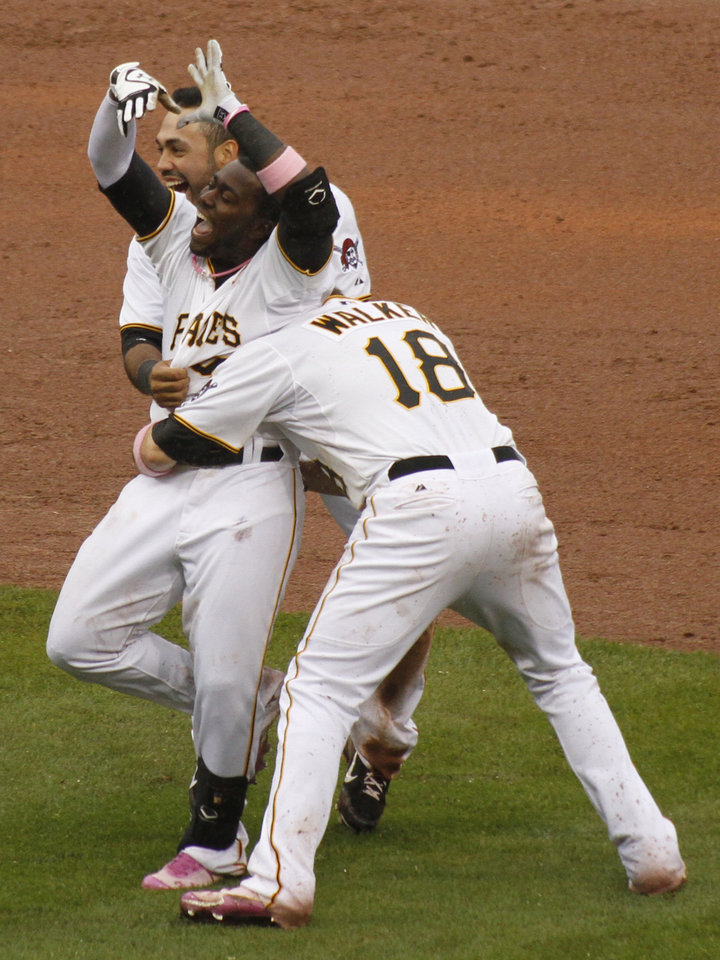 Photo -   Pittsburgh Pirates' Josh Harrison, center, is greeted by teammates Pedro Alvarez, left, and Neil Walker (18) after driving in Clint Barmes from second with the game-winning run against the Houston Astros in the 12th inning of a baseball game on Sunday, May 13, 2012, in Pittsburgh. The Pirates won 3-2. (AP Photo/Keith Srakocic)