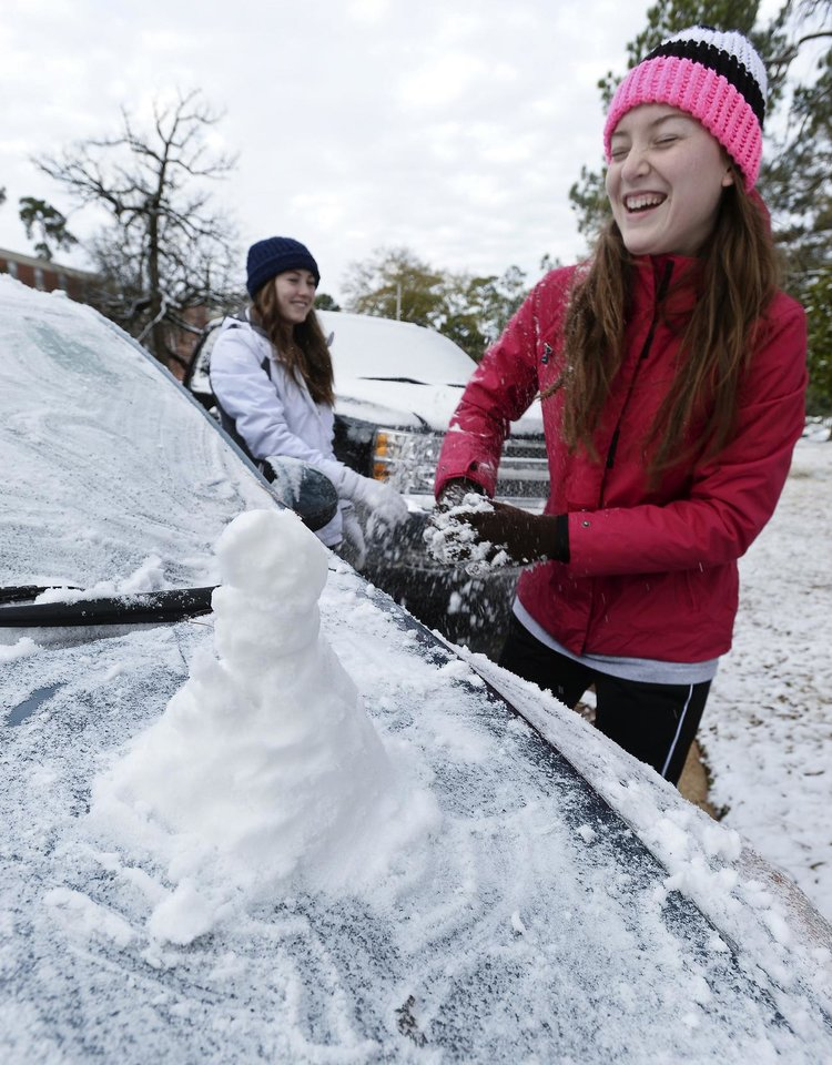 Photo - Stephen F. Austin State freshmen Tara Ramsey, left, of Mont Belvieu, Texas, and Makenzie Dickins of Livingston take a snowball break while building a miniature snowman on the hood of a car Friday, Jan. 24, 2014, on the SFA campus in Nacogdoches, Texas. The girls were enjoying an unexpected day off after campus offices were closed and classes were canceled due to a winter storm that moved through the area overnight. (AP Photo/The Daily Sentinel, Andrew D. Brosig) MANDATORY CREDIT