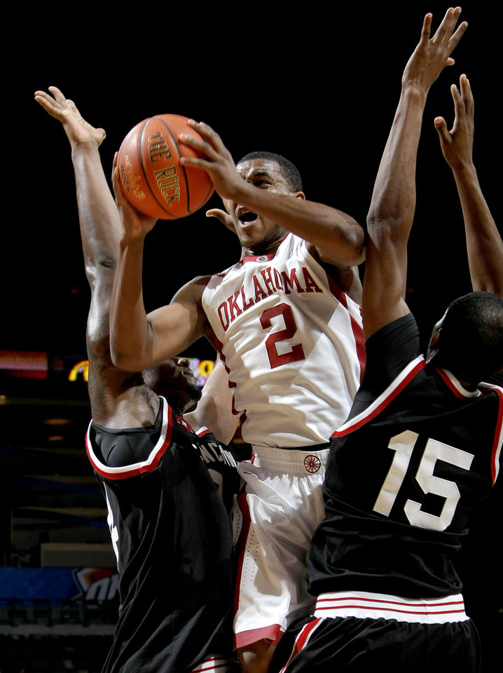 Photo - OU's Steven Pledger tries to shoot the ball from between Cincinnati's Yancy Gates, left, and Darnell Wilks during the All-College Classic basketball game between the University of Oklahoma and Cincinnati at the Oklahoma City Arena on Saturday, December 18,  2010.   Photo by Bryan Terry, The Oklahoman