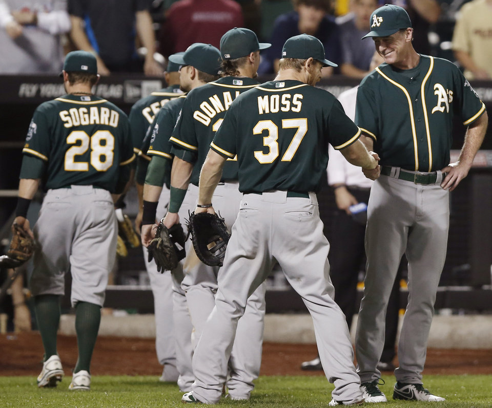 Photo - Oakland Athletics manager Bob Melvin, far right, congratulates Oakland Athletics first baseman Brandon Moss (37) after the Athletics 8-5 victory over the New York Mets in an interleague baseball game in New York, Wednesday, June 25, 2014. (AP Photo/Kathy Willens)