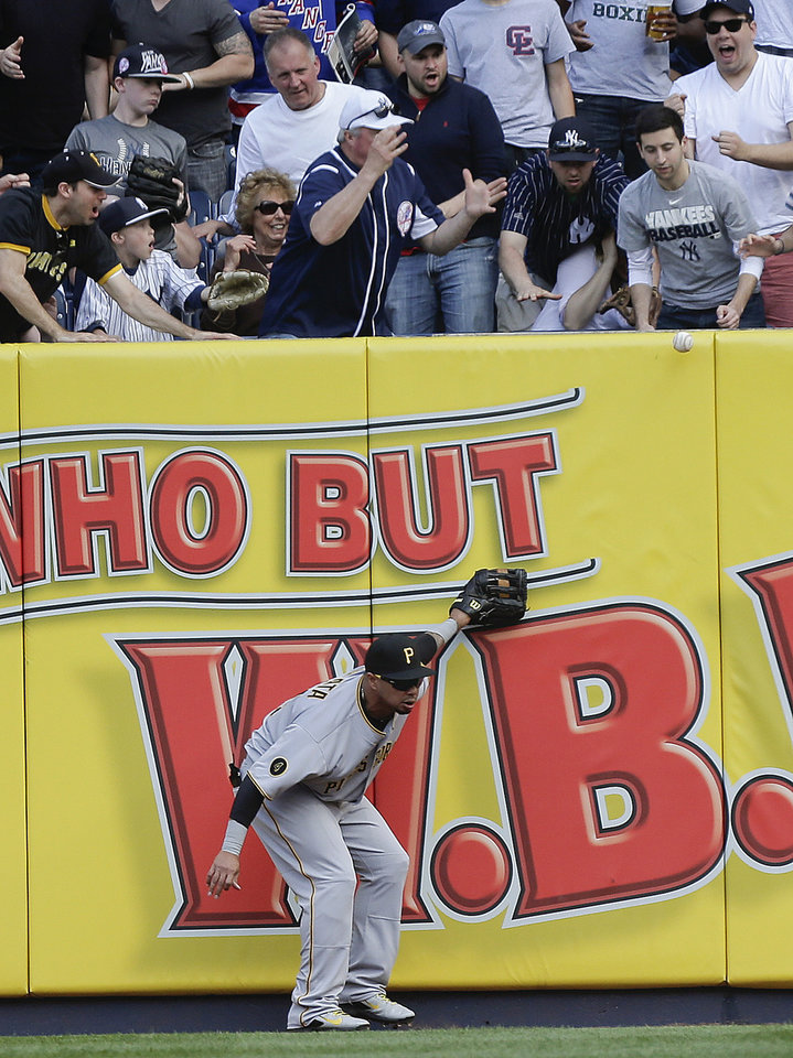 Photo - A home run ball hit by New York Yankees' Mark Teixeira bounces back onto the field after Pittsburgh Pirates right fielder Jose Tabata was unable to make the catch during the first inning of a baseball game, Saturday, May 17, 2014, in New York. Derek Jeter scored on the homer. (AP Photo/Julie Jacobson)