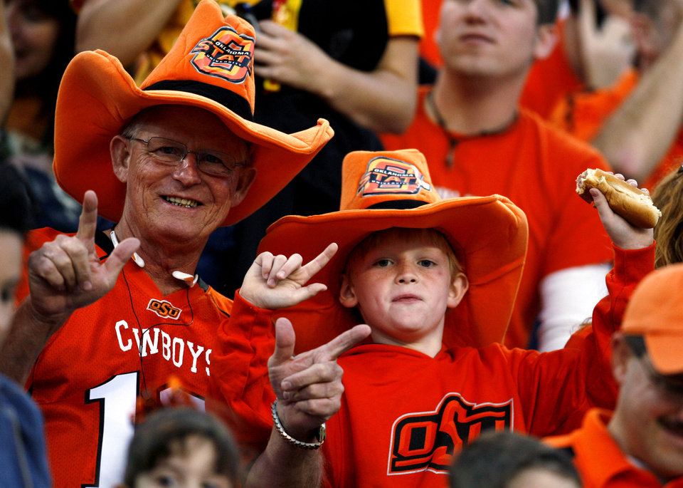 Photo - Oklahoma State fans Tom Alford and his grandson Connor McSwain cheer the Cowboys at the college football game between Oklahoma State University and Baylor University at Floyd Casey Stadium in Waco, Texas, Saturday, Nov. 17, 2007. BY STEVE SISNEY, THE OKLAHOMAN