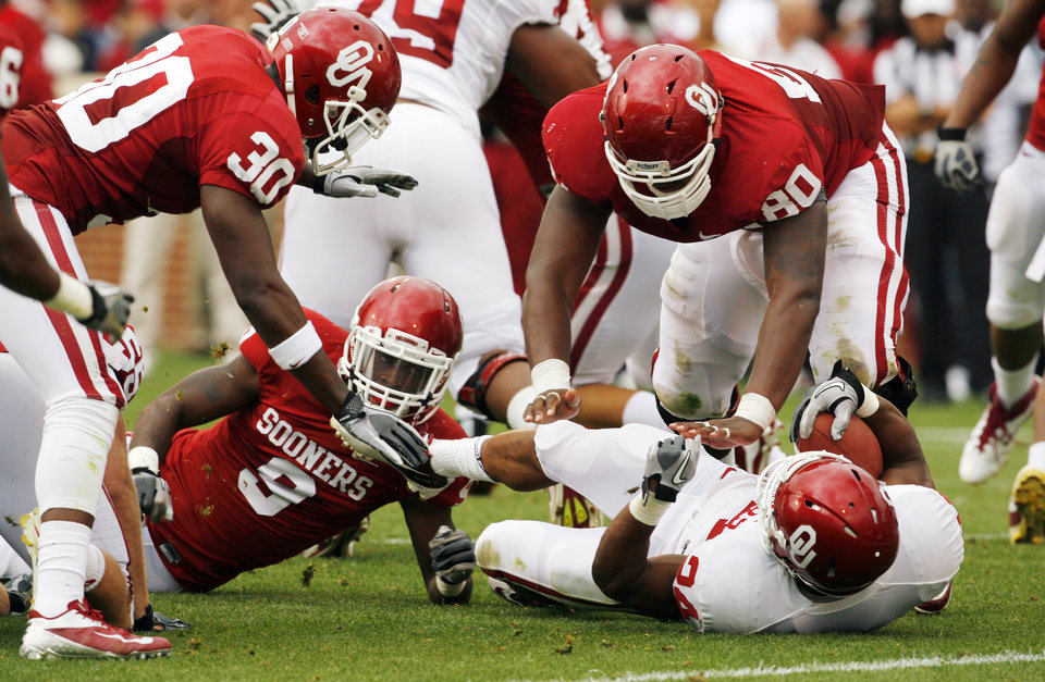 Javon Harris (30), Gabe Lynn (9) and Jordan Phillips (80) bring down Brennan Clay (24) during the University of Oklahoma (OU) football team\'s annual Red and White Game at Gaylord Family/Oklahoma Memorial Stadium on Saturday, April 14, 2012, in Norman, Okla. Photo by Steve Sisney, The Oklahoman