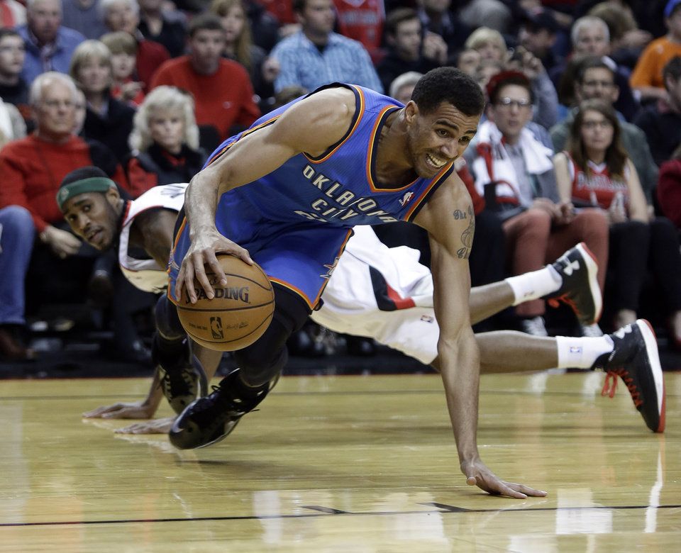 Photo - Oklahoma City Thunder guard Thabo Sefolosha, right, from Switzerland, tries to maintain control of the ball after being tripped by Portland Trail Blazers guard Will Barton during the first quarter of an NBA basketball game in Portland, Ore., Friday, April 12, 2013. (AP Photo/Don Ryan) ORG XMIT: ORDR103
