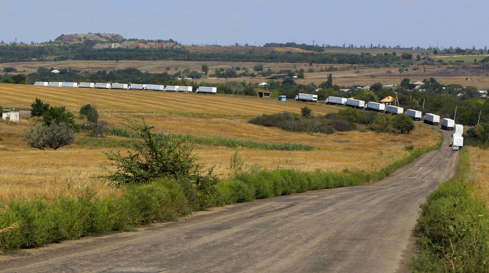 Photo - The first trucks of the convoy roll on the main road to Luhansk near the village of Uralo-Kavkaz, after it passed the border post at Izvaryne, eastern Ukraine, Friday, Aug. 22, 2014. The first trucks in a Russian aid convoy crossed into eastern Ukraine on Friday, seemingly without Kiev's approval, after more than a week's delay amid suspicions the mission was being used as a cover for an invasion by Moscow. (AP Photo/Sergei Grits)