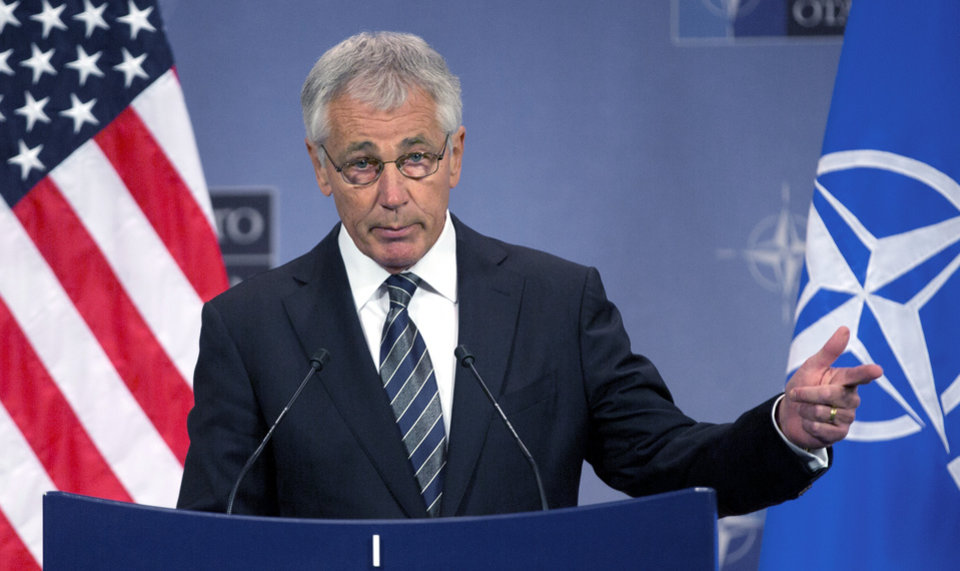 Photo - FILE - In this Oct. 23, 2013 file photo, Secretary of Defense Chuck Hagel speaks during a media conference after a meeting of NATO defense ministers at NATO headquarters in Brussels. Defense Secretary Chuck Hagel on Thursday, Oct. 31, 2013 sharply criticized U.S. states that are defying the Pentagon by refusing to allow National Guard facilities to issue ID cards that enable same-sex spouses of military members to claim benefits. (AP Photo/Virginia Mayo, File)