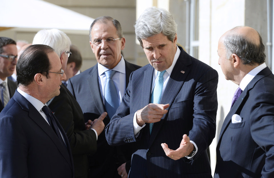 Photo - French President Francois Hollande, left, U.S. Secretary of State John Kerry, center, and  French Foreign Minister Laurent Fabius, right, talk together while German Foreign Minister Frank-Walter Steinmeier, background left, Russian Foreign Minister Sergey Lavrov background right, talk together behind them during a break of a meeting at the Elysee Palace in Paris, Wednesday, March 5, 2014. Top diplomats from the West and Russia trying to find an end to the crisis in Ukraine are gathering in Paris on Wednesday as tensions simmered over the Russian military takeover of the strategic Crimean Peninsula. (AP Photo/Alain Jocard, Pool)