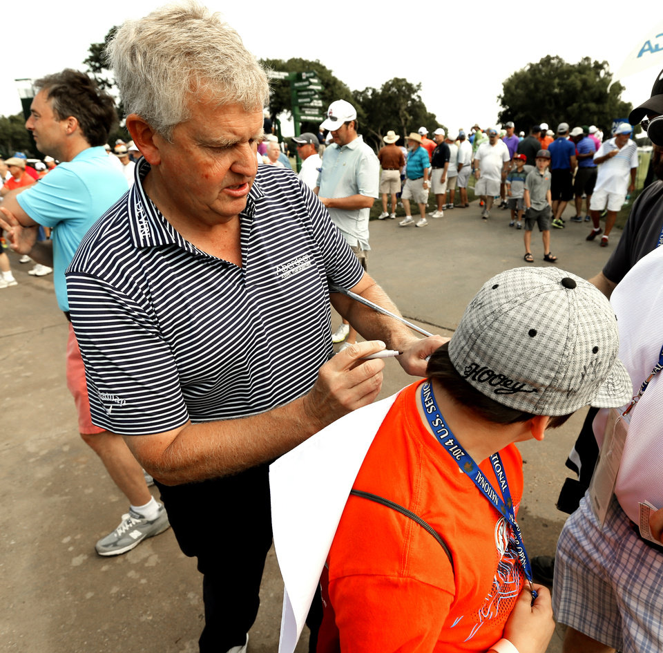 Photo - Colin Montgomerie gives an autograph to Keagan Knight, 12, before the first round of the U.S. Senior Open Championship golf tournament at Oak Tree National in Edmond, Okla. on Thursday, July 10, 2014. Photo by Steve Sisney, The Oklahoman
