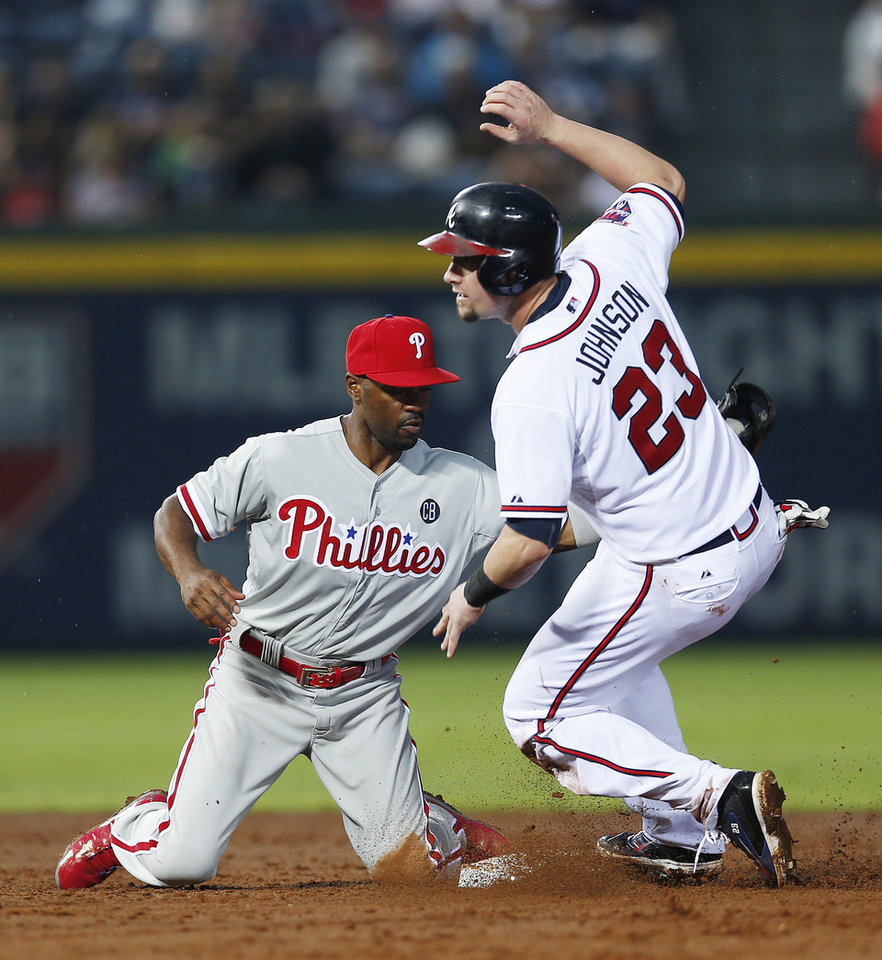 Photo - Atlanta Braves' Chris Johnson (23) steals second base as Philadelphia Phillies shortstop Jimmy Rollins (11) applies the late tag in the third inning of a baseball game in Atlanta, Friday, July 18, 2014. (AP Photo/John Bazemore)