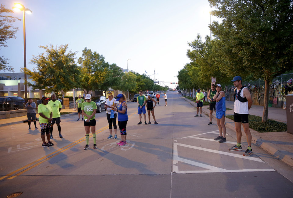 Photo - Runners pause for 168 seconds of silence before running the route of the Oklahoma City Memorial Marathon in Oklahoma City,  Sunday, April 26, 2020.  The 20th Oklahoma City Memorial Marathon was delayed until October because of Covid-19. [Sarah Phipps/The Oklahoman]